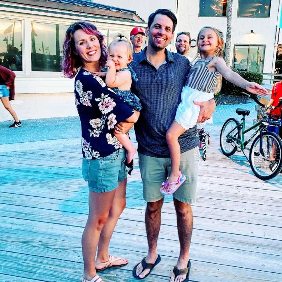 Married couple pose for a family photo with their two daughters on a boardwalk