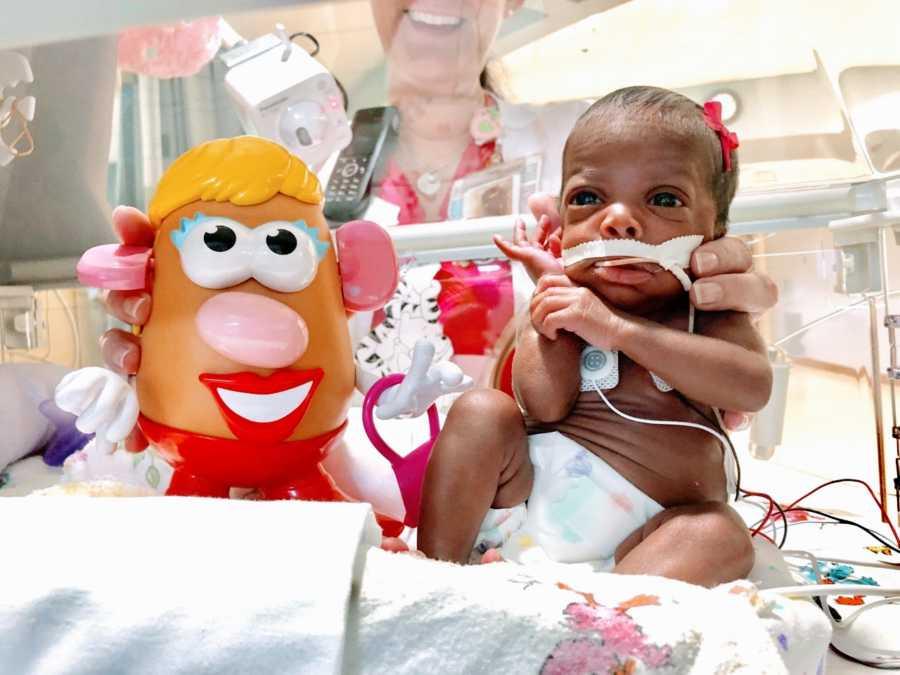 Nurse takes photo of preemie baby next to Potato Head figure to show size difference