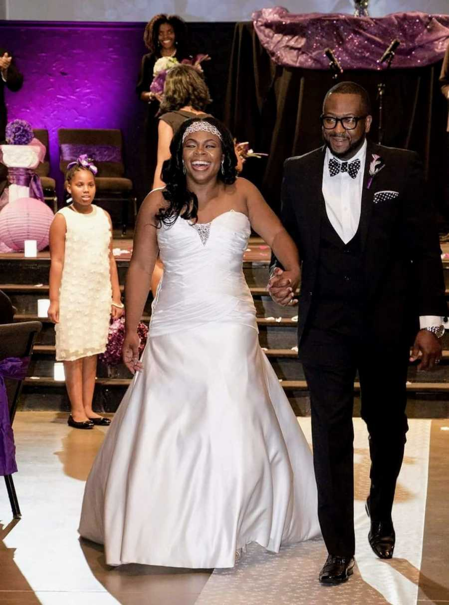 Couple walk hand-in-hand to the dance floor during their wedding reception