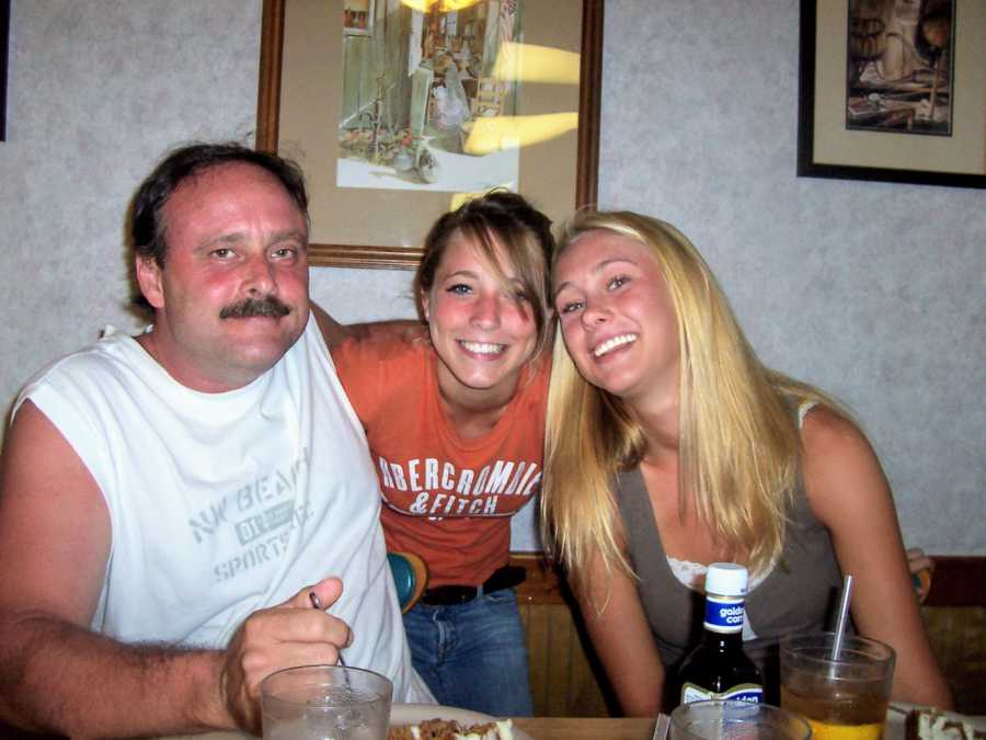 Father with arms around two daughters sitting in kitchen at dinner table