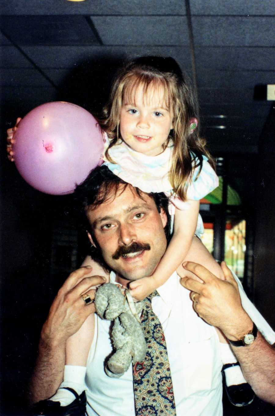 Father holding daughter on shoulders and the daughter is holding a pink balloon