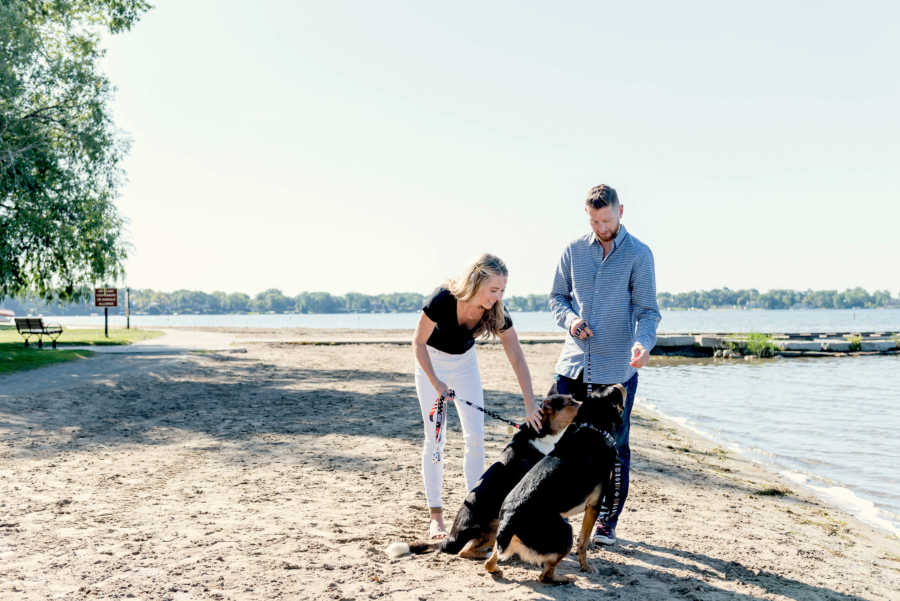 Husband and wife with two dogs on leashes at beach