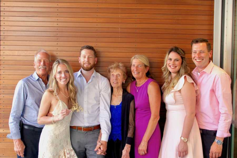 Wedding photo of bride and groom with family in front of wood-slatted wall