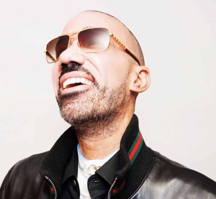 Man wearing leather jacket and sunglasses smiling
