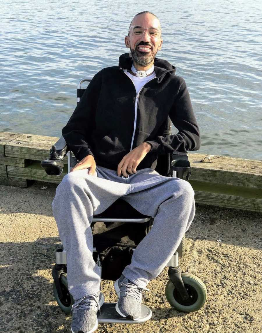 Man in wheelchair by lake smiling