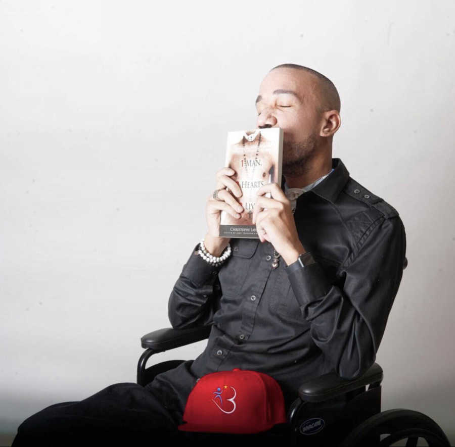 Man in wheelchair kissing book he wrote