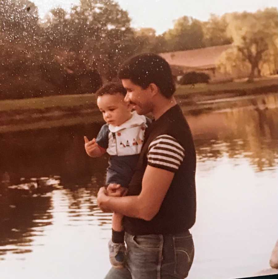 Father holding young son by lake