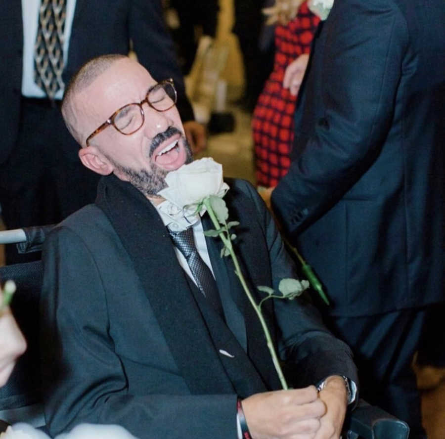 Man at wedding using flower as microphone