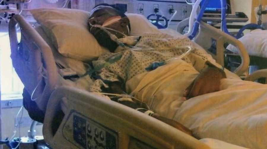 Man lying in hospital bed hooked up to machines