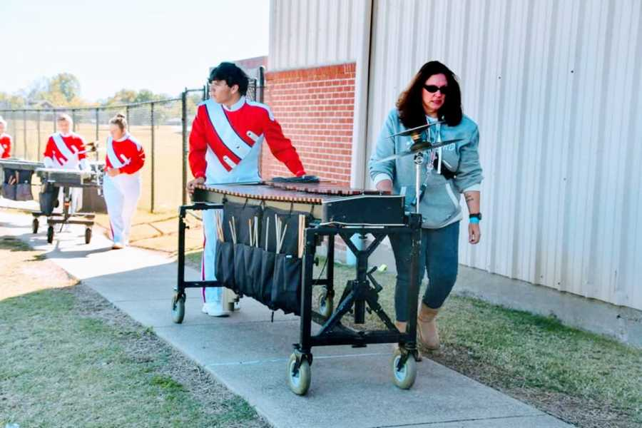 Mom helps her high school son push his instrument for a marching band performance