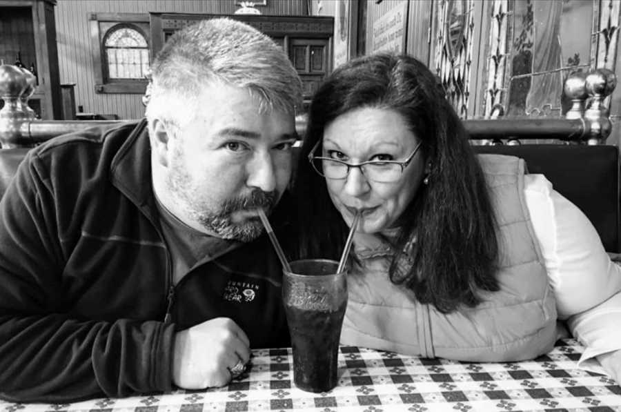 Woman sits in an old-fashioned diner and shares a coke with her husband