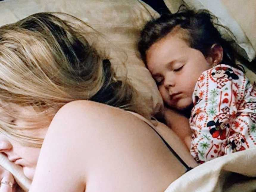 Exhausted mom sleeps with her daughter after a long day