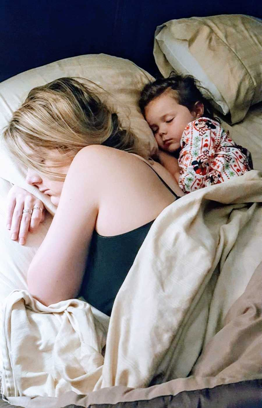 Mom shares a pillow with her daughter while they both sleep after a long day