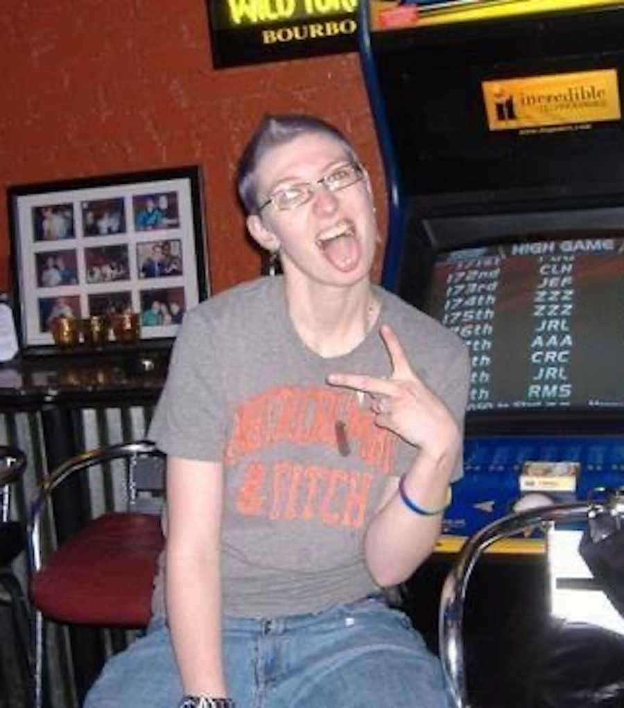 person in arcade with peace sign