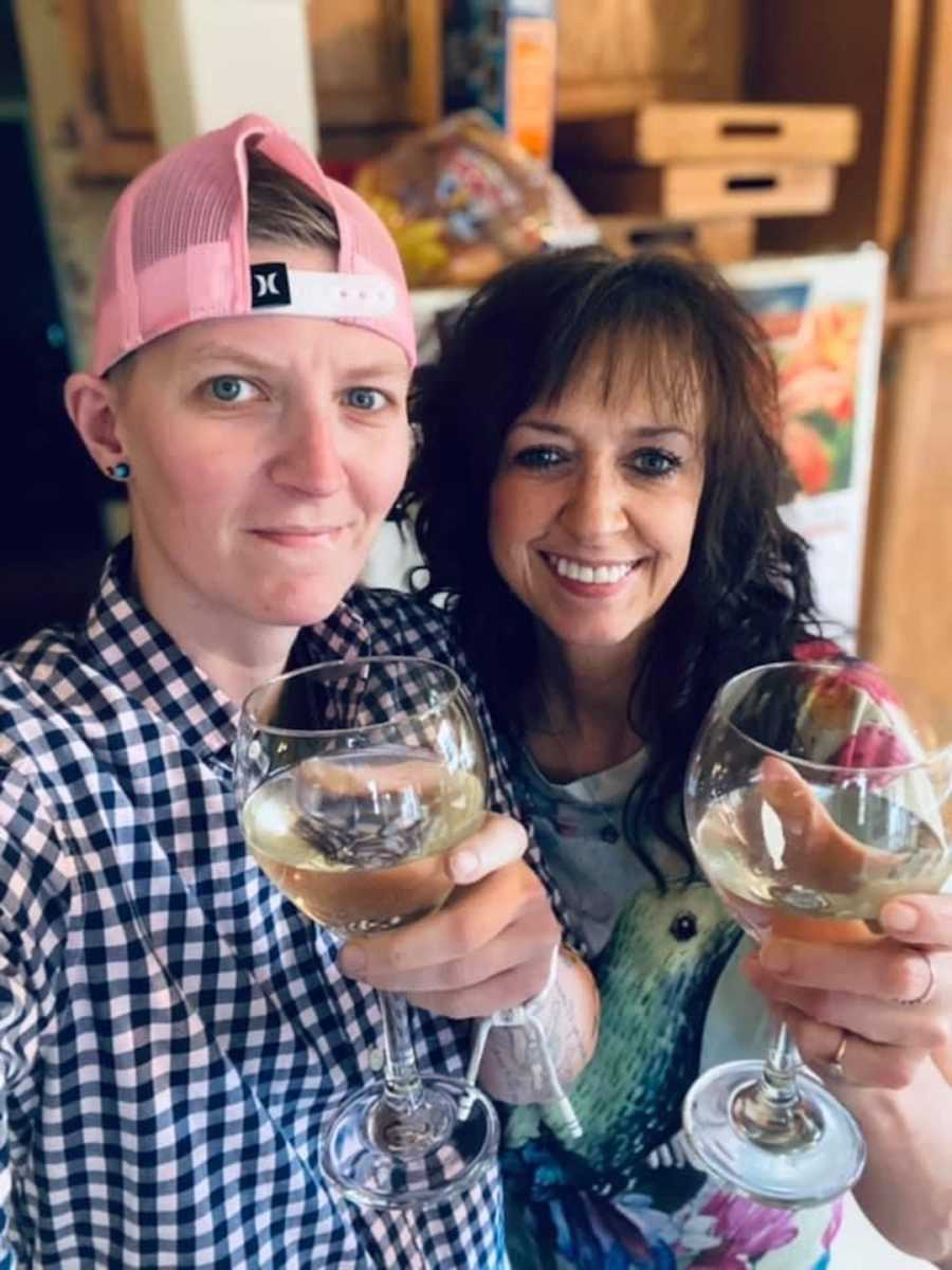 person in baseball cap holding wine glass, woman holding wine glass