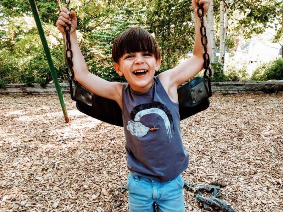 Child at playground on swingset smiling