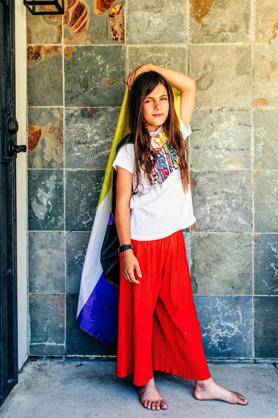 Child wearing rainbow colors and Pride shirt posing in front of stone wall