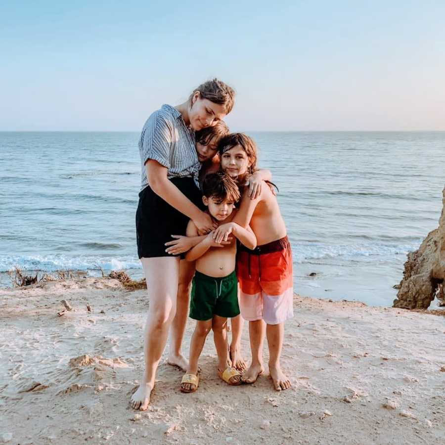 Mother hugging her three children at the beach