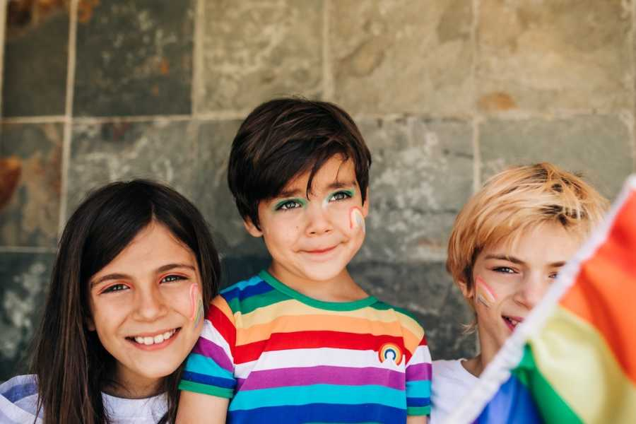 Three siblings celebrating Pride wearing rainbow colors and holding the Pride flag