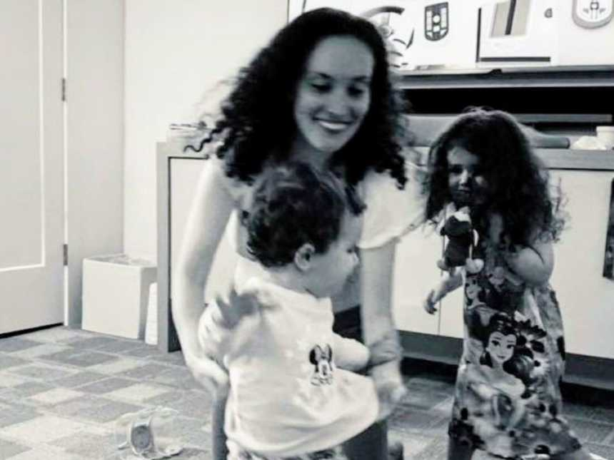 Mom smiles while her kids run and dance around her in the living room