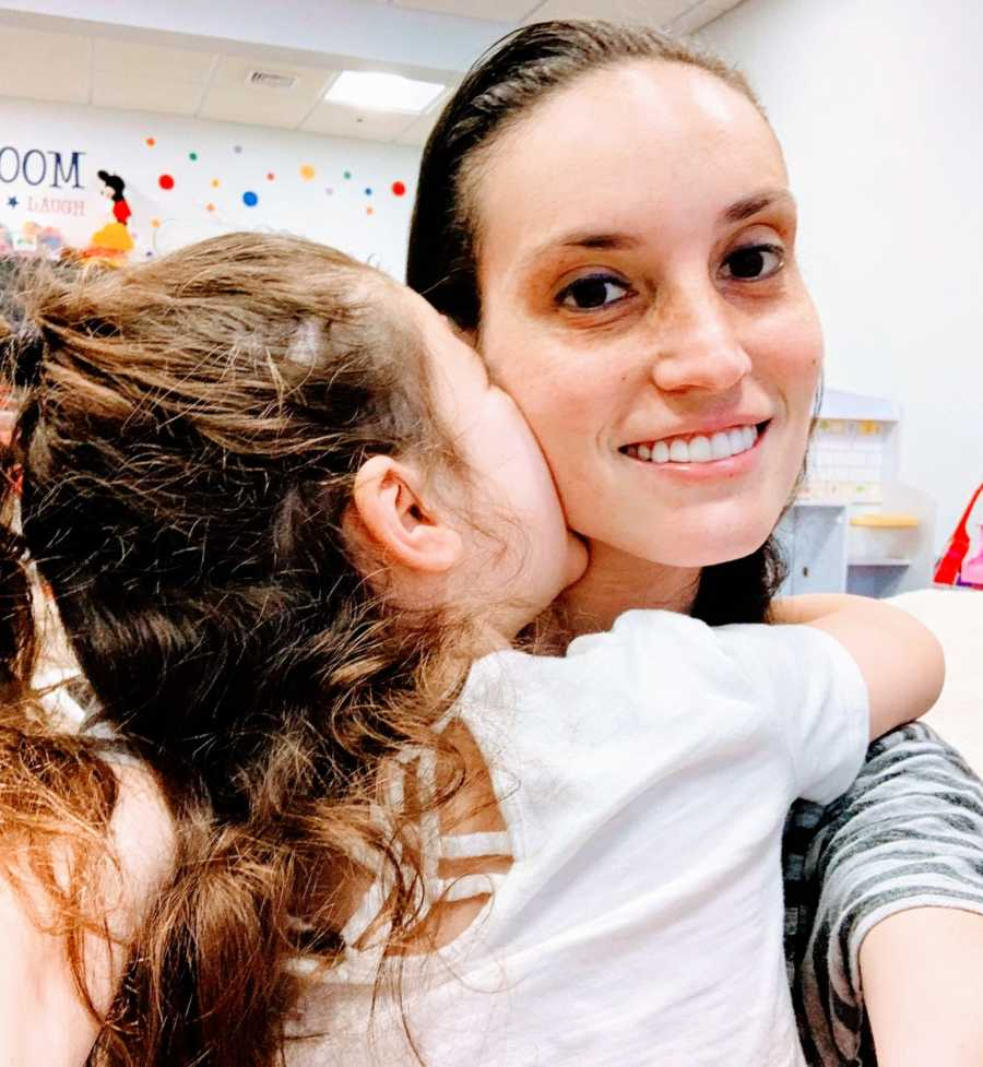 Mom smiles while her daughter hugs her and gives her a kiss on the cheek