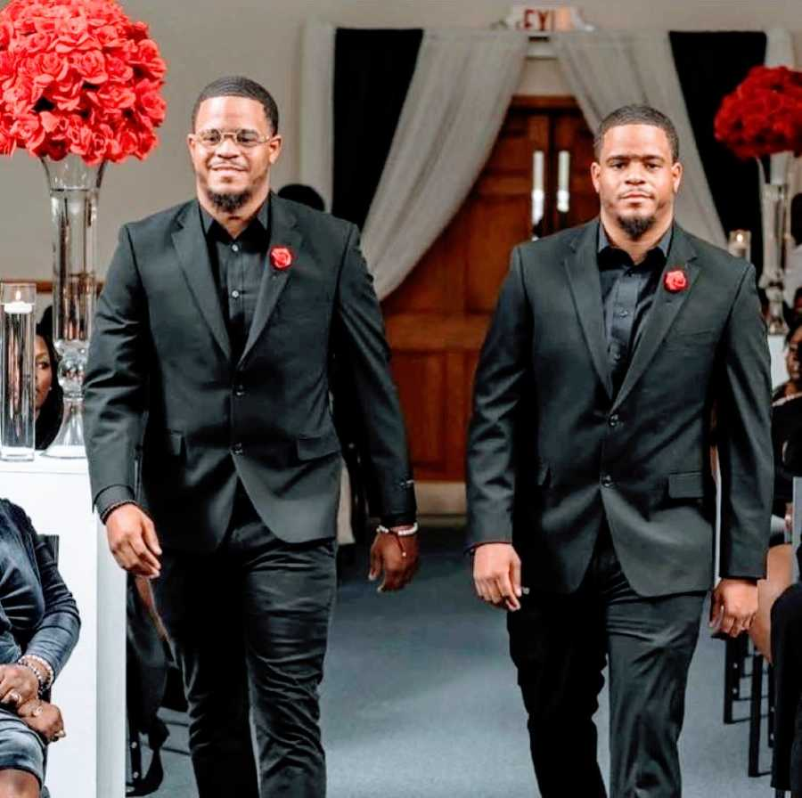 Twin brothers in matching suits get candid photo at an event