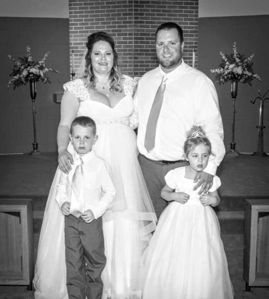 Newly weds take a photo with their two children before their wedding reception
