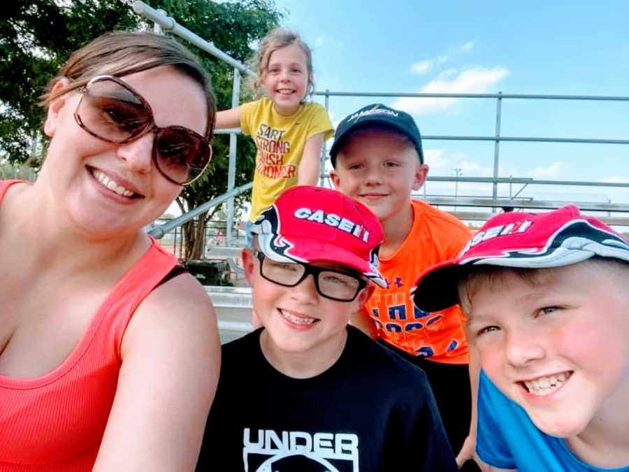 Mom takes a selfie with her kids and step kids while sitting in the bleachers