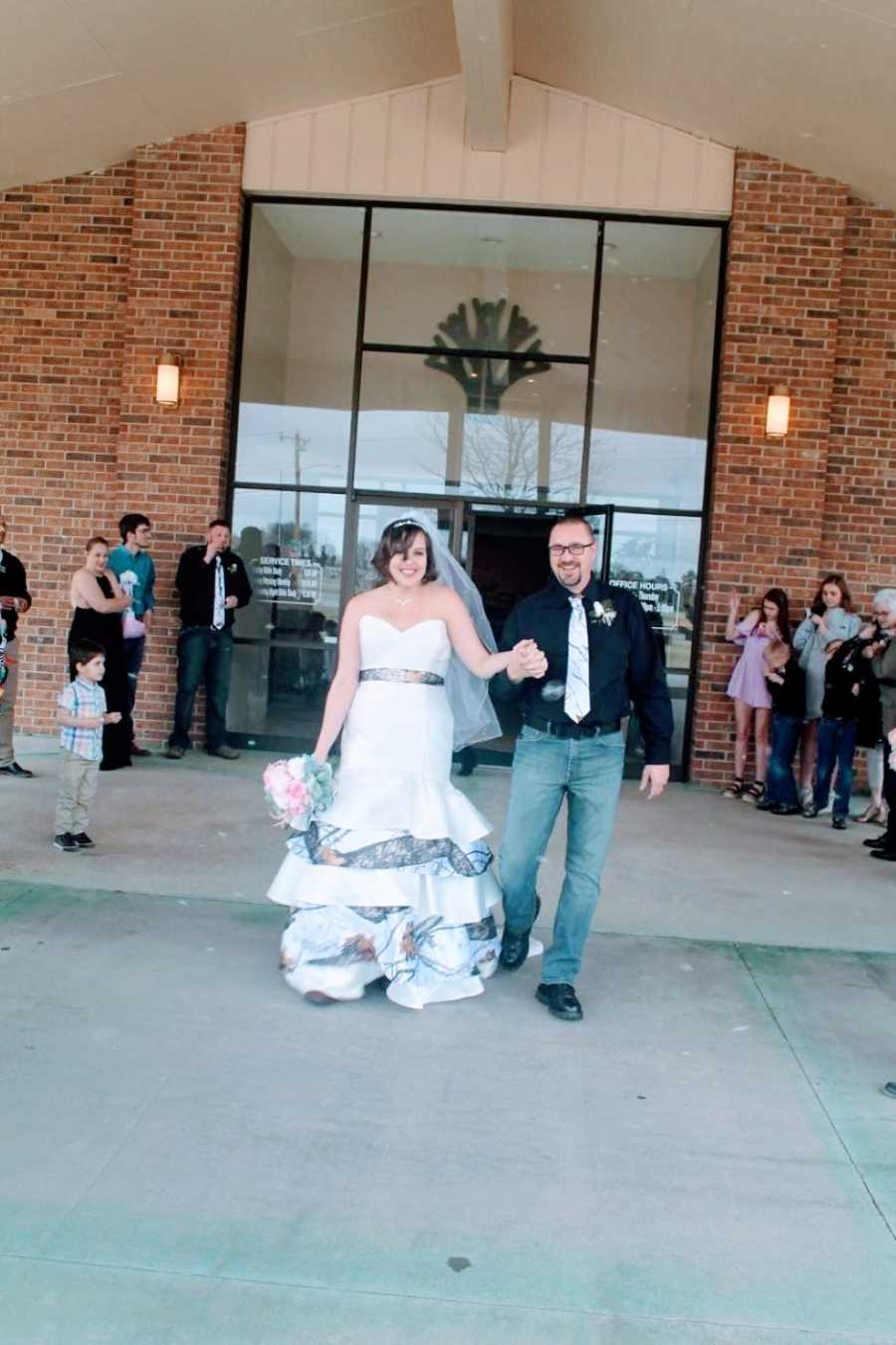Newly weds walk out of their wedding reception hand-in-hand with big smiles