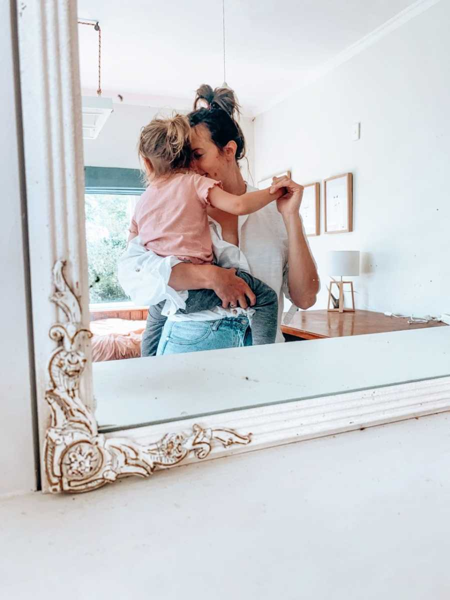 Mom snuggles and dances around with her toddler in her arms