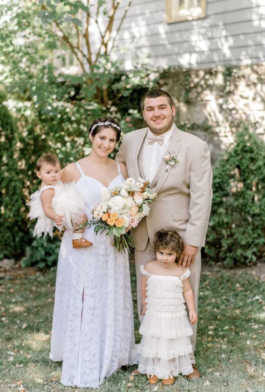 Young couple take family photo at their wedding with their two daughters