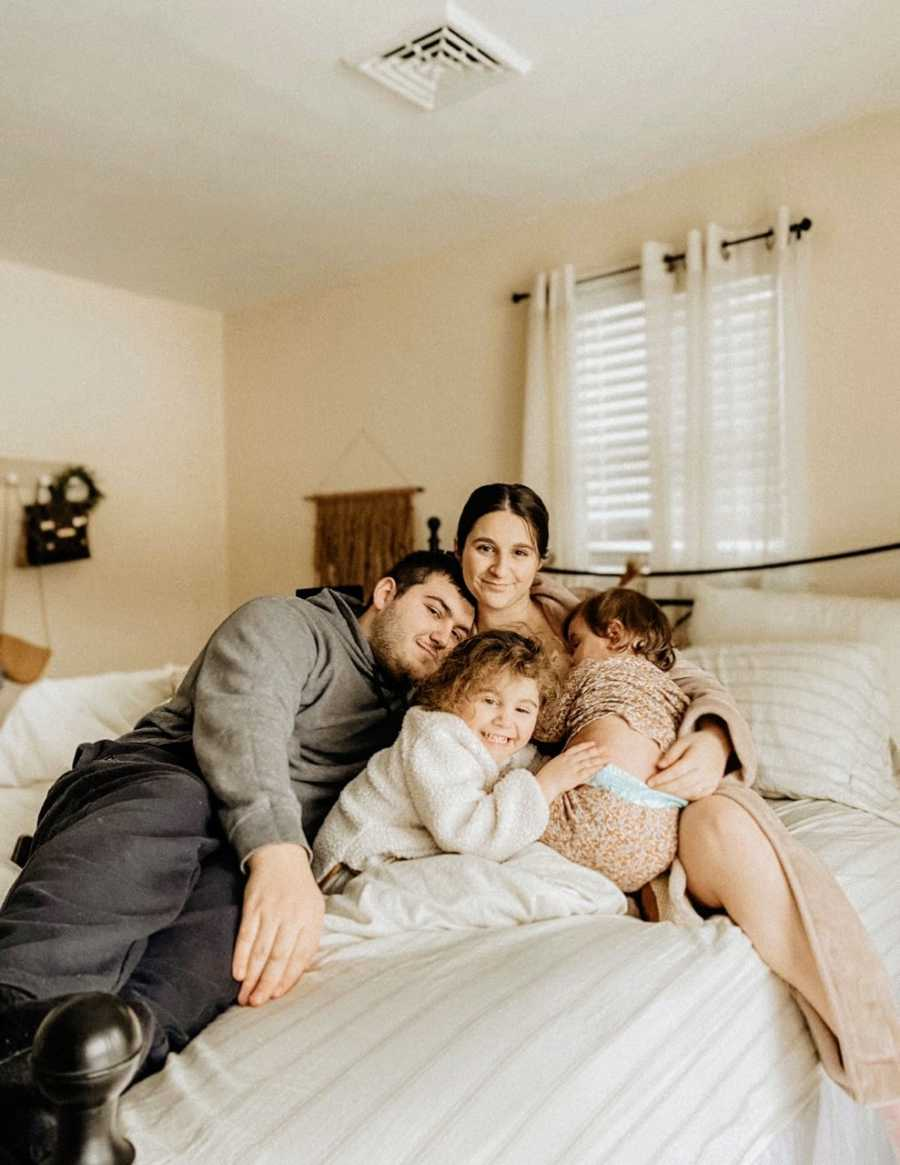 Family of four take a photo together, all piled up in bed together and cuddling