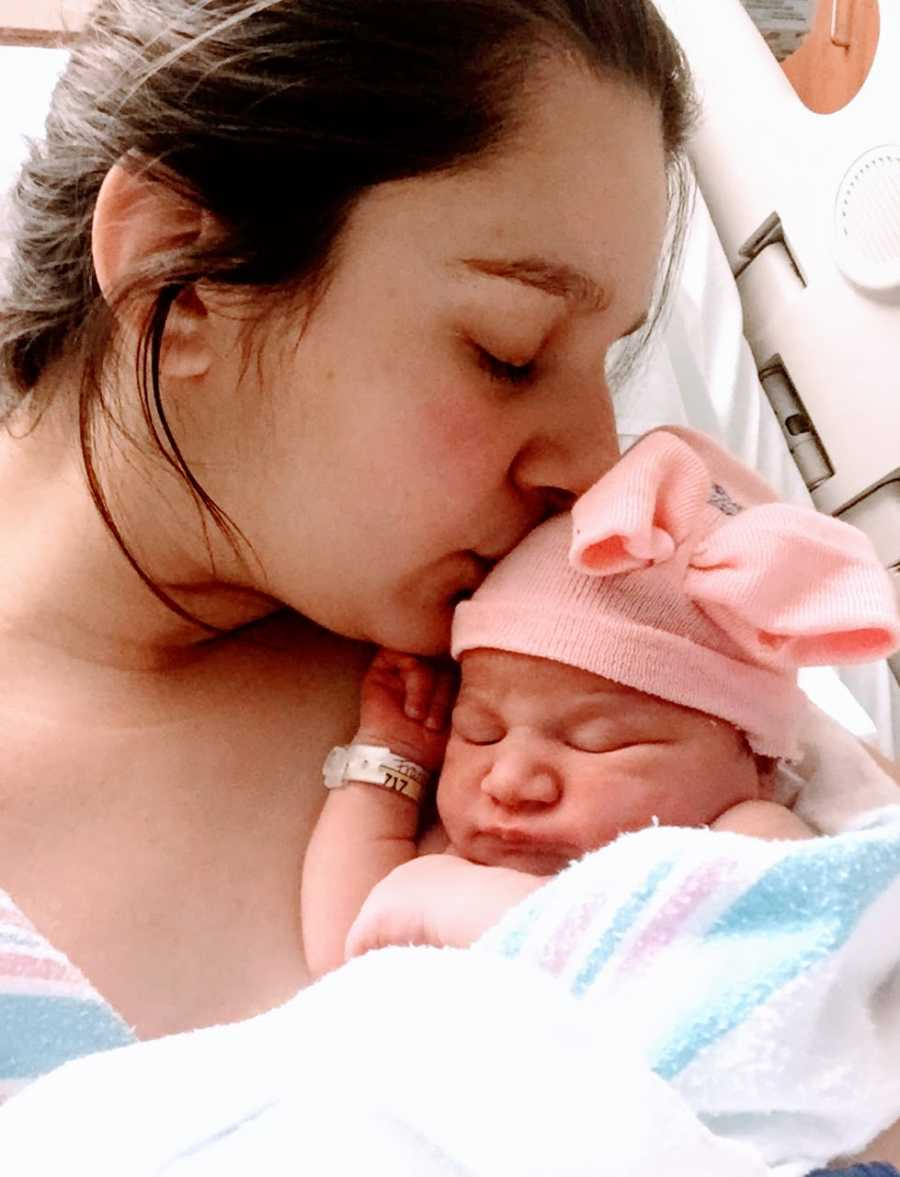 Teen mom takes a photo kissing her newborn daughter on the forehead while laying in a hospital bed after birth