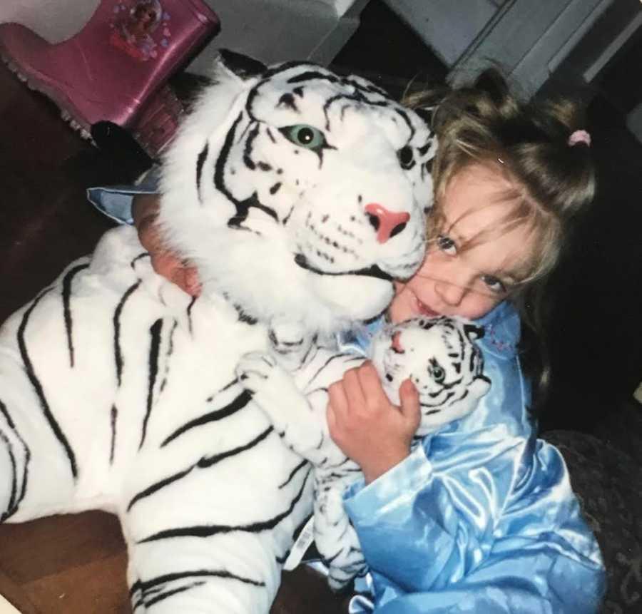 girl holding stuffed tiger