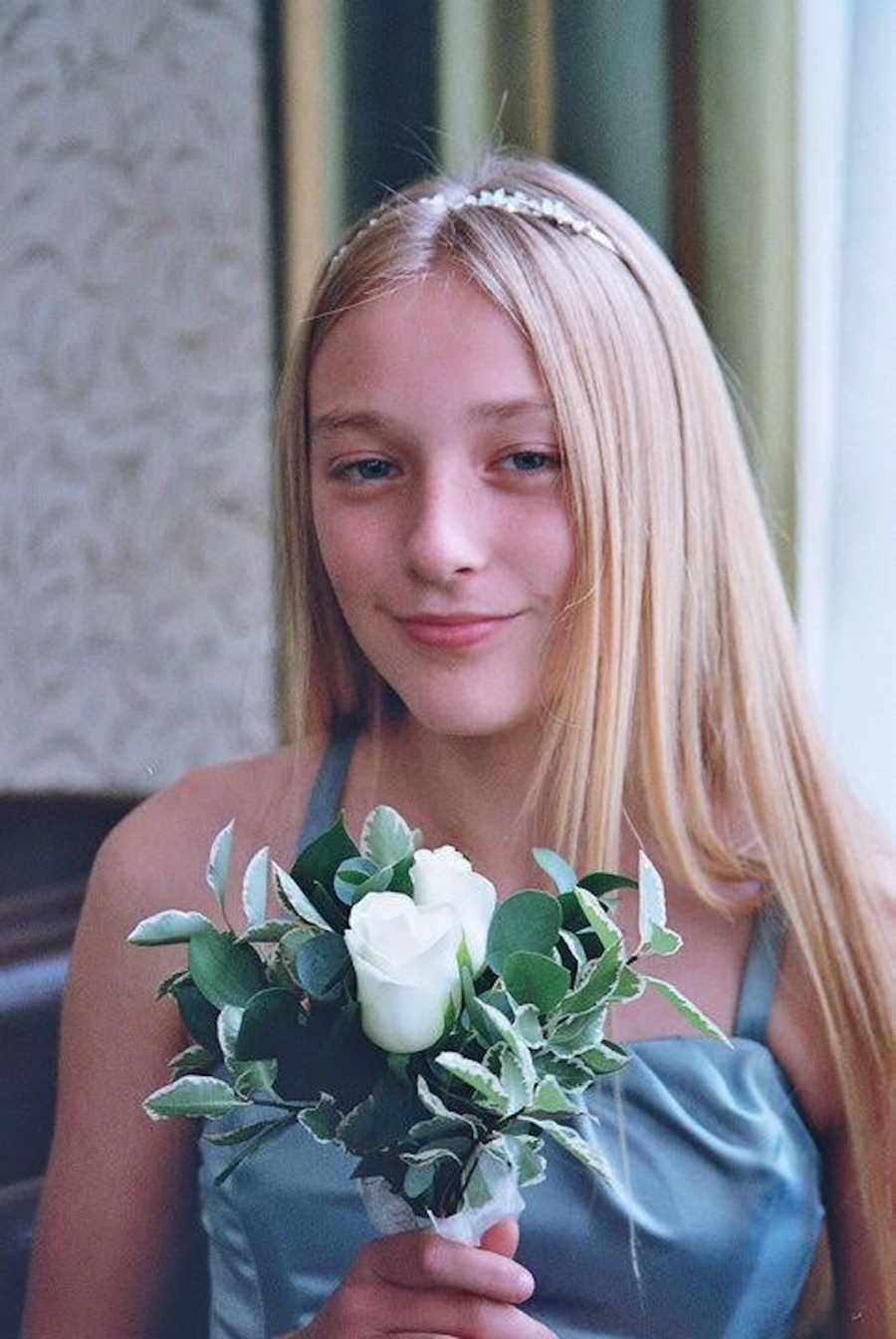 young girl smiling, holding a bouquet of flowers