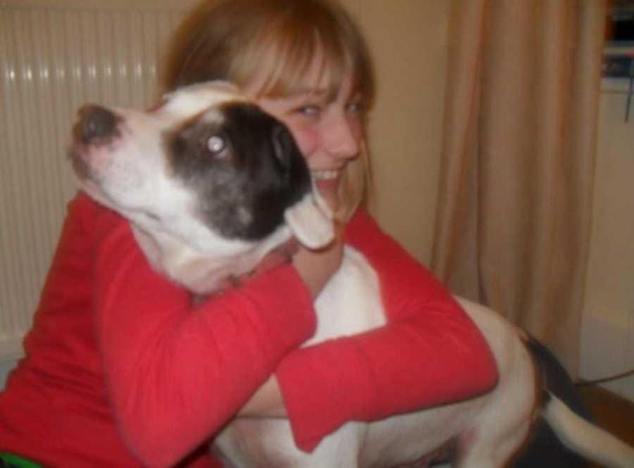 teenaged girl hugging a dog