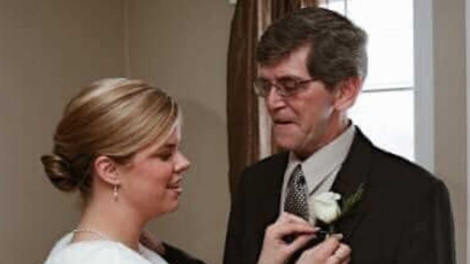 woman with her father, pinning his suit