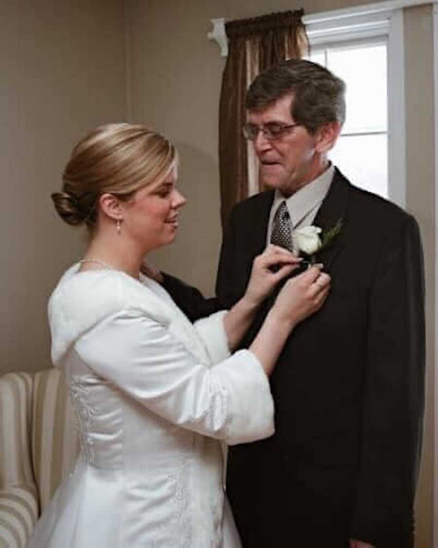 woman pinning a flower on dad's suit