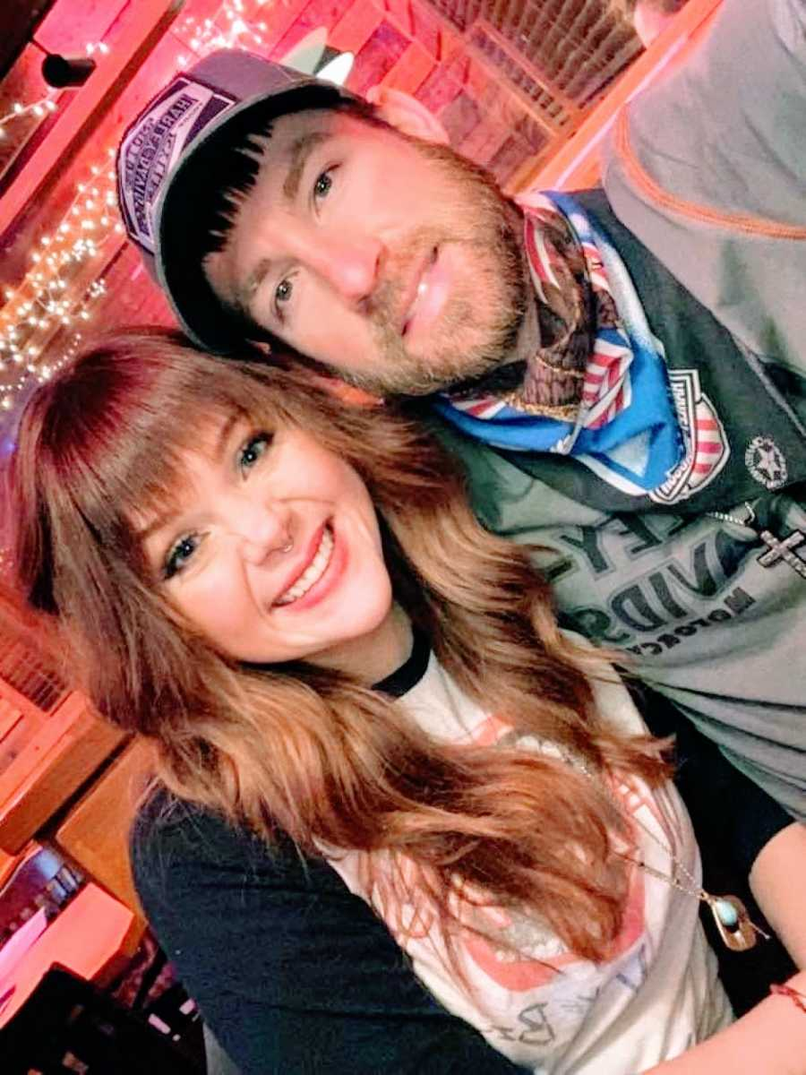 Couple smile and take a selfie together as they wait for their food at Applebee's