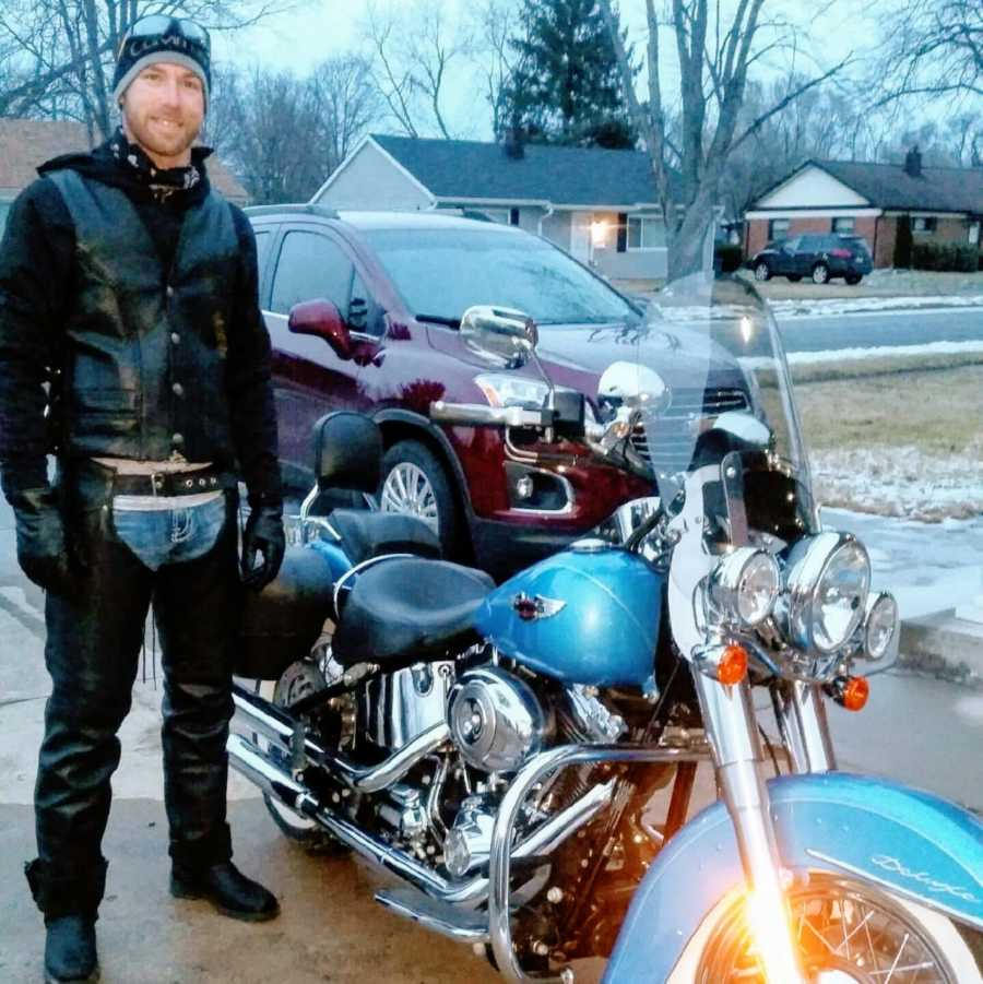 Man wears leather outfit next to his Harley Davidson motorcycle