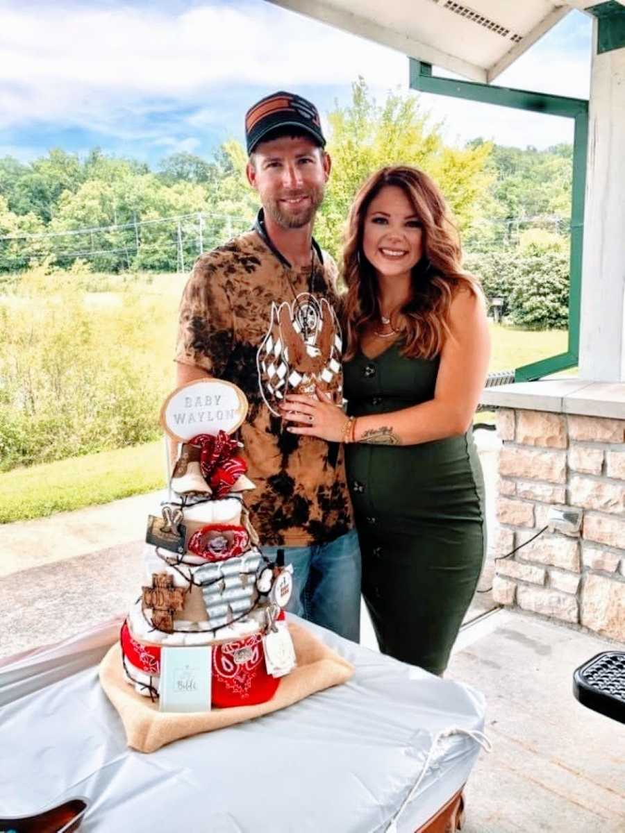 Newly engaged couple take a photo at their baby shower