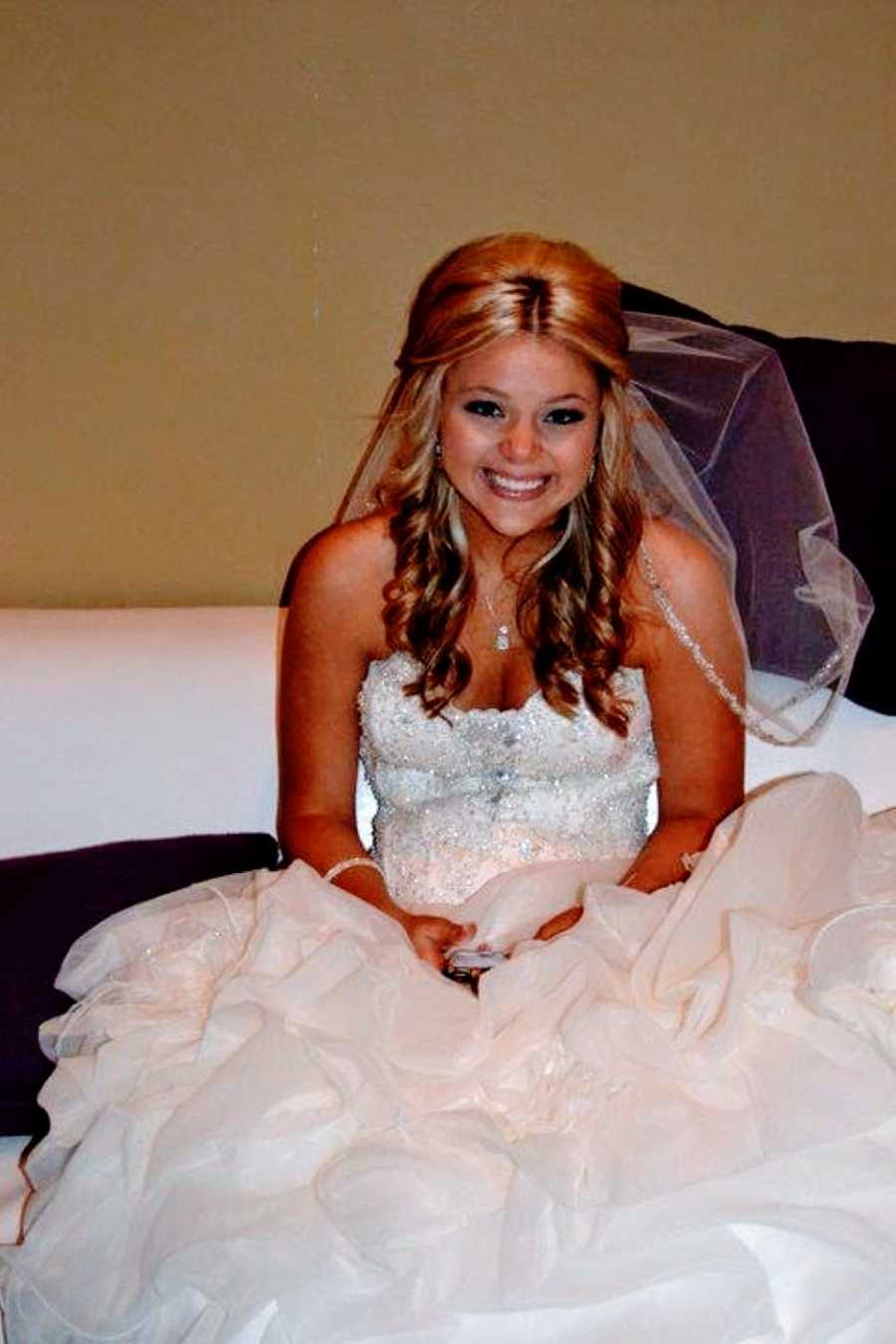 Woman sits on the floor and smiles in her wedding dress