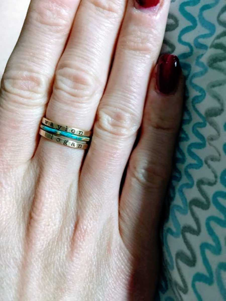 Woman shows off her new stackable rings that have her sons' names engraved on them