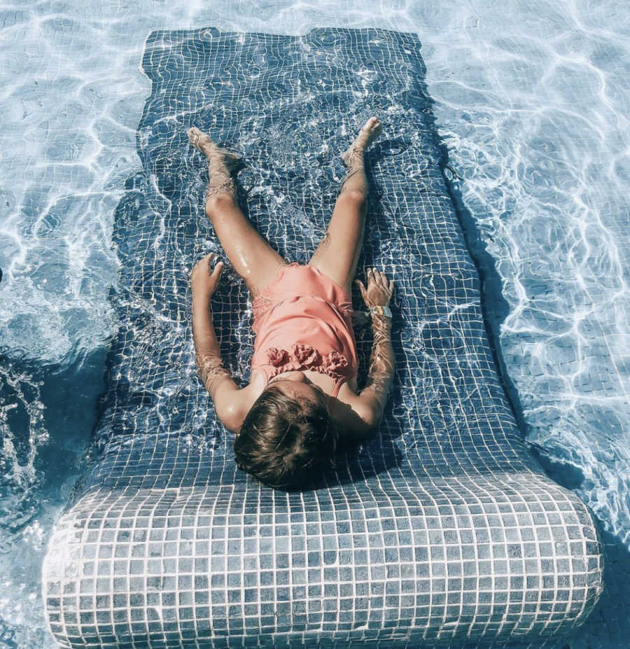 Child laying in pool