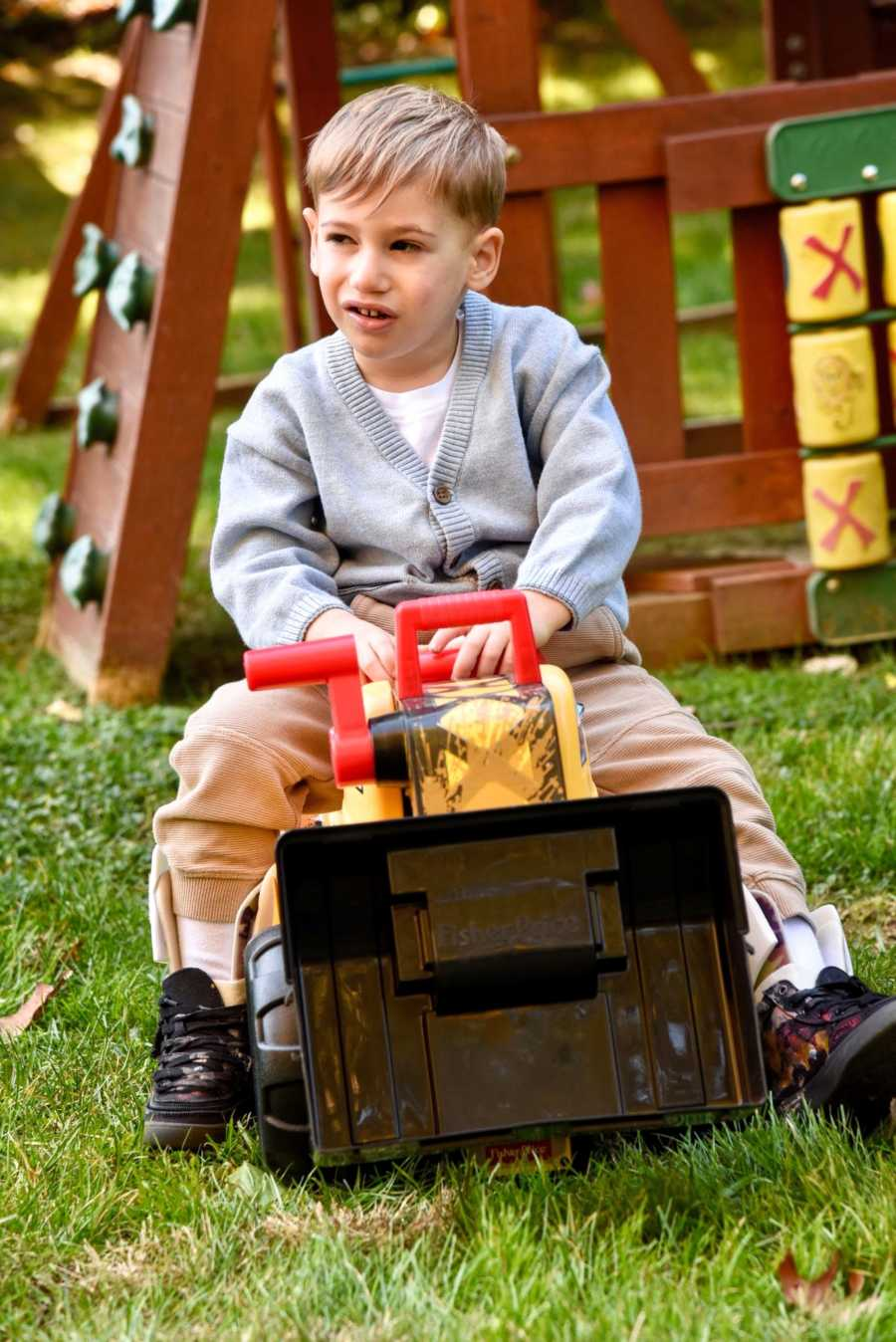 Young boy in gray sweater sits on a toy truck outside on a playground