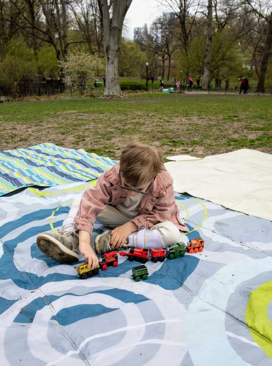 Young boy with glasses sits on a blanket in a park and plays with toy trains