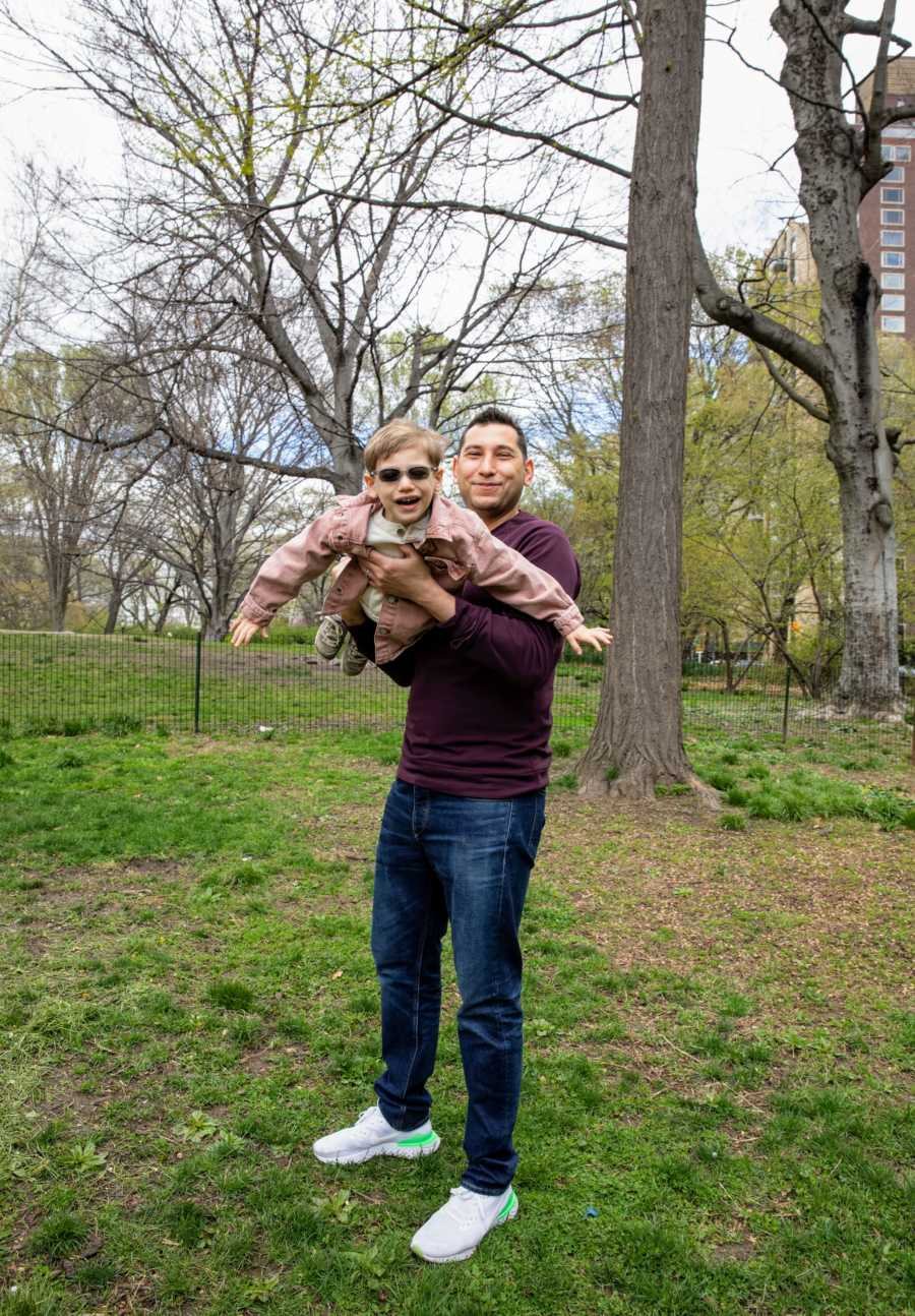 Dad plays with his son born with CMT while taking family photos at the park