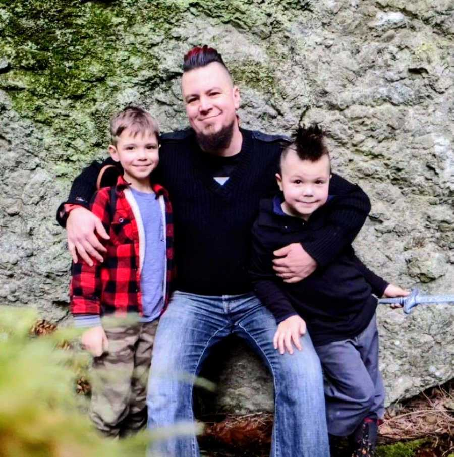 Dad with a red and black mohawk hugs his two sons for a photo while hiking