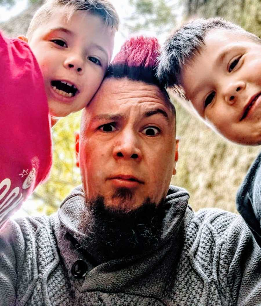Dad with a red mohawk takes a goofy selfie with his two sons