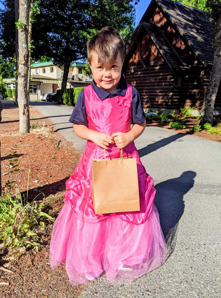 Little boy smiles shyly while wearing a hot pink princess dress